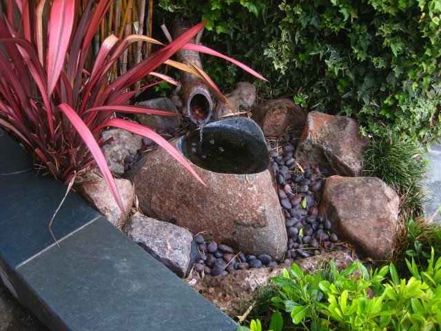 asian style front fountain blending with landscaping