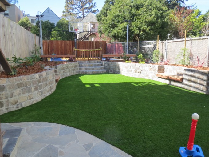 The finished backyard landscaping project: sports centered, with strong turf, basketball court and room for soccer