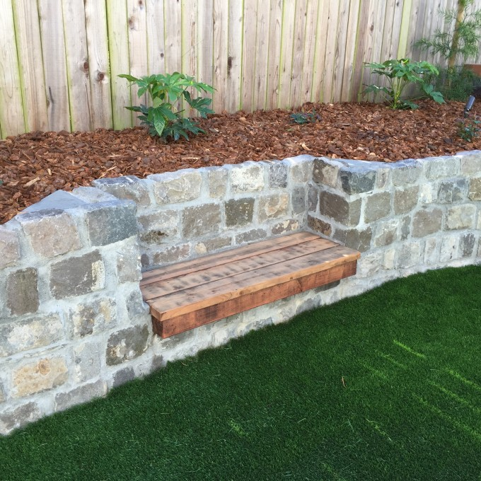 Redwood bench set in recycled cobblestone retaining wall