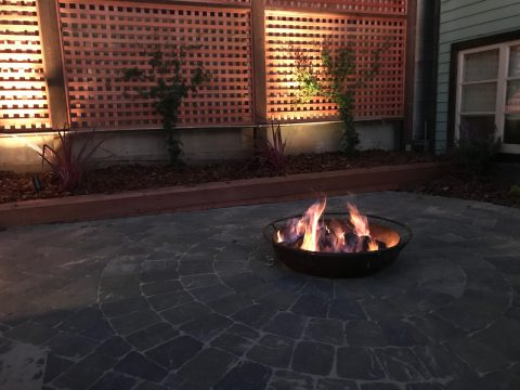 Backyard Landscape Project: Lower patio, made with interlocking pavers, holds a fire pit made from an Iron dish, customized to accept a natural gas fire ring